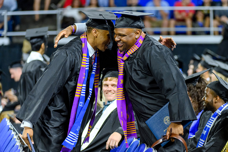 Two members of MTSU's Class of 2019 congratulate each other on reaching their goals Aug. 10 during the university's summer 2019 commencement ceremony in Murphy Center. MTSU's fall 2019 commencement ceremonies are set Saturday, Dec. 14.(MTSU photo by J. Intintoli)