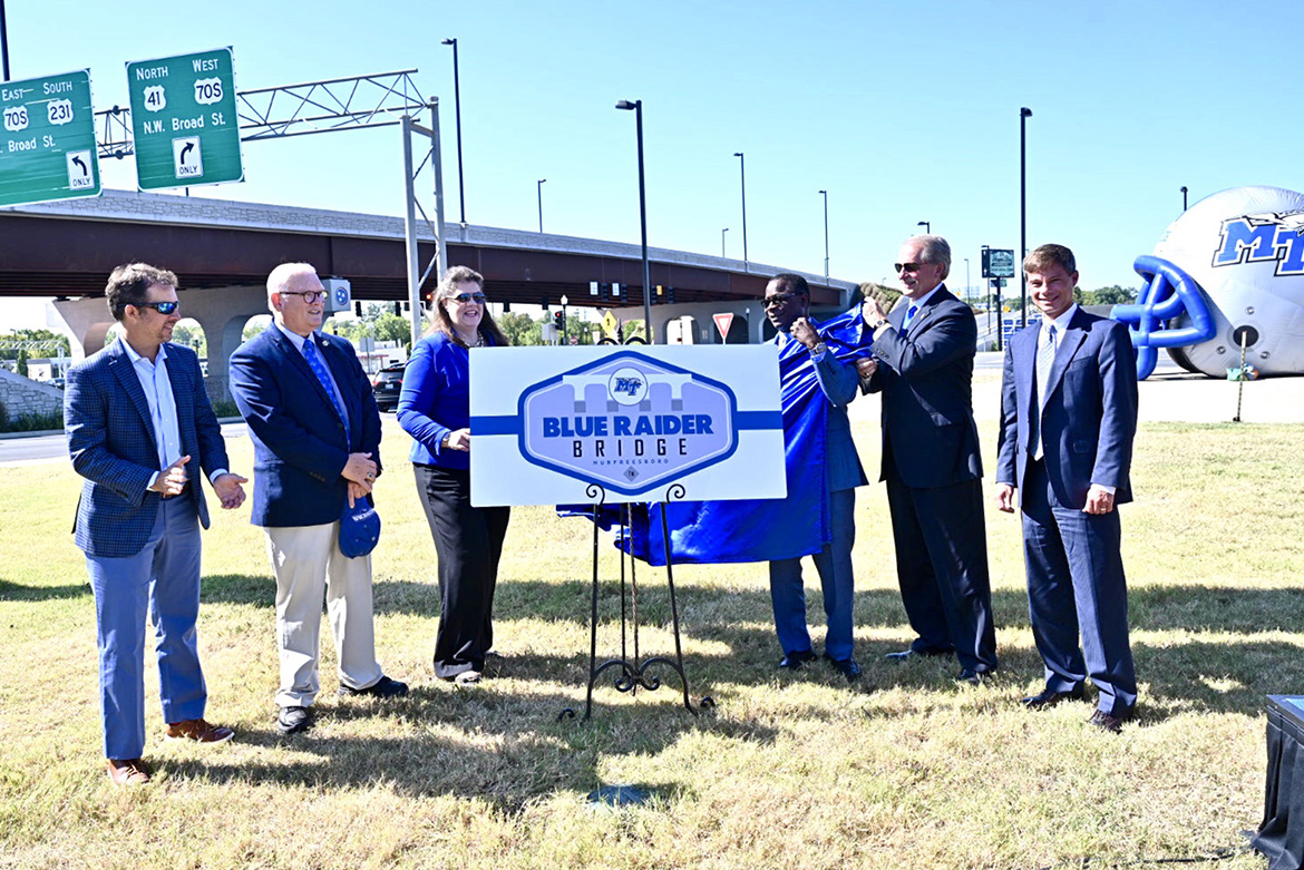 MTSU and area officials unveil a commemorative sign at the Thursday, Sept. 5, dedication ceremony of the newly named Blue Raider Bridge in the background. Pictured, from left, are Murfreesboro Mayor Shane McFarland, Rutherford County Commission Pettus Read, state Sen. Dawn White, MTSU President Sidney A. McPhee, Rutherford County Mayor Bill Ketron, and state Rep. Charlie Baum, also an MTSU economics professor. (MTSU photo by J. Intintoli)