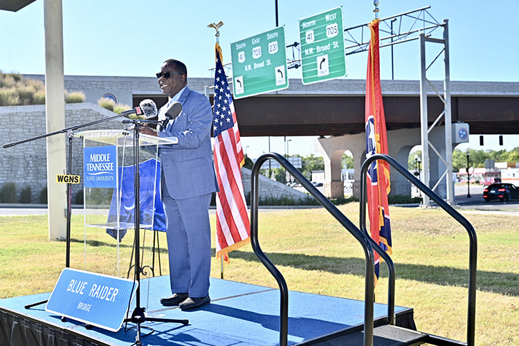 MTSU President Sidney A. McPhee praises the 'town-and-gown' partnership between the university and local community at the Thursday, Sept. 5, dedication ceremony of the newly named Blue Raider Bridge in the background. (MTSU photo by J. Intintoli)