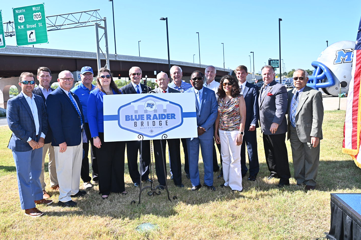 A host of MTSU, Murfreesboro, Rutherford County and state officials stand with a commemorative sign at the Thursday, Sept. 5, dedication ceremony of the newly named Blue Raider Bridge in the background. (MTSU photo by J. Intintoli)