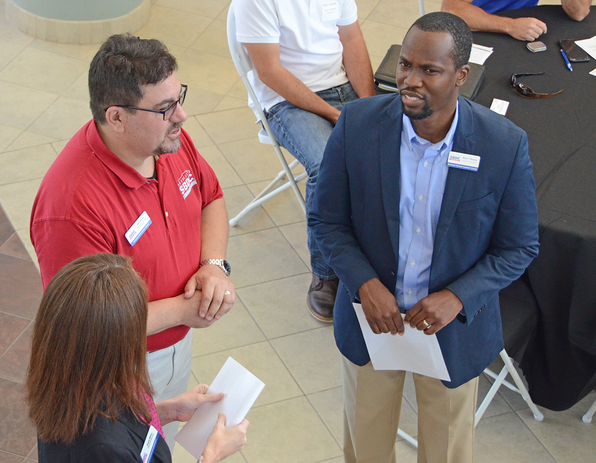 Attendees at the inaugural Tennessee Craft Beer and Spirit Distilleries International Sales Opportunities Forum Aug. 27 in the MTSU Miller Education Center atrium confer before the start of the event that drew more than 60 people from across the state. (MTSU photo by Randy Weiler)