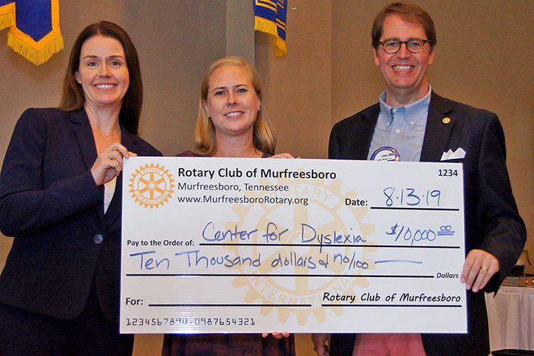 Jennifer Flipse, left, director of The Tennessee Center for the Study and Treatment of Dyslexia, accepts a ceremonial $10,000 check from the Rotary Club of Murfreesboro from the club's 2018-2019 president Melissa Cassidy, center, and current club president Rev. Dr. John A. Hinkle at an Aug. 13 luncheon at the Stones River Country Club. (Photo provided)
