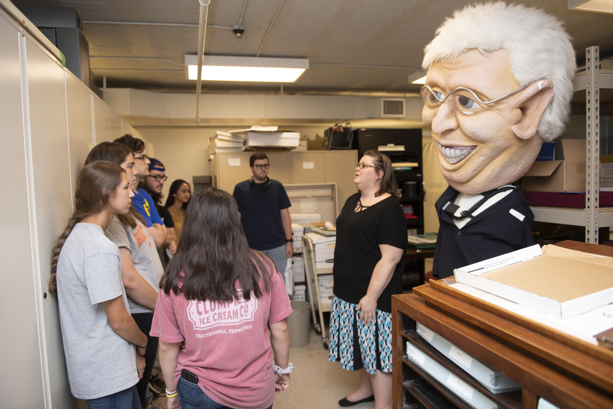 As an extra-large caricature of former Tennessee Gov. Don Sundquist looms in the background, Donna Baker, university archivist in the Albert Gore Sr. Research Center on the MTSU campus, tells Blackman Collegiate Academy seniors about the various types of archiving is performed at the center. The Blackman High students visited MTSU Tuesday, Sept. 10. (MTSU photo by James Cessna)
