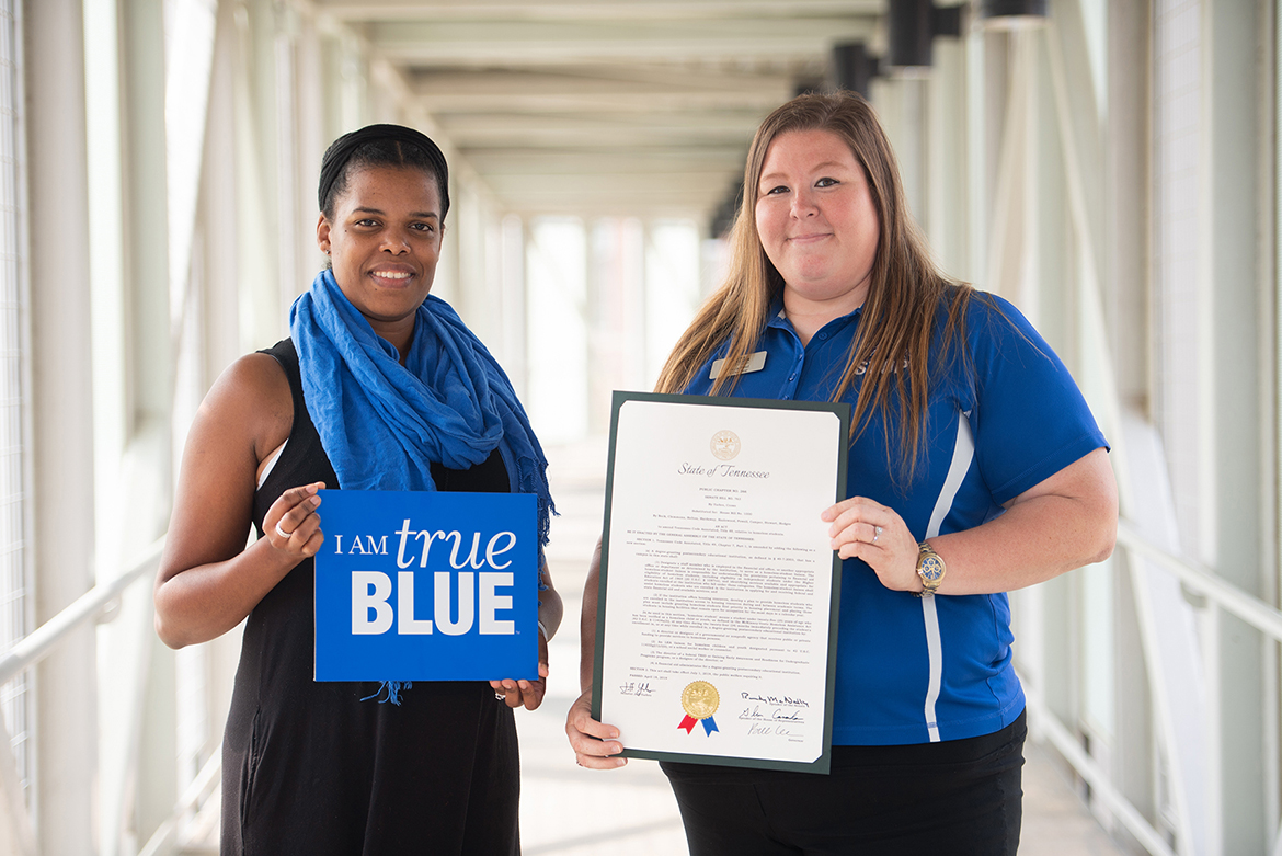 Becca Seul, right, associate director at MT One Stop at MTSU, holds a framed commemorative copy of the new state law to require state-supported colleges and universities to develop programs to help homeless students. Seul and Danielle Rochelle, left, coordinator of outreach and support programs for MT One Stop, testified at the state Capitol in Nashville, Tenn., in support of the bill when it was in committee. (MTSU photo by James Cessna)