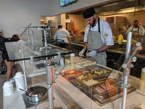 A cook works on the daily sandwich in front of students with locally sourced ingredients.
