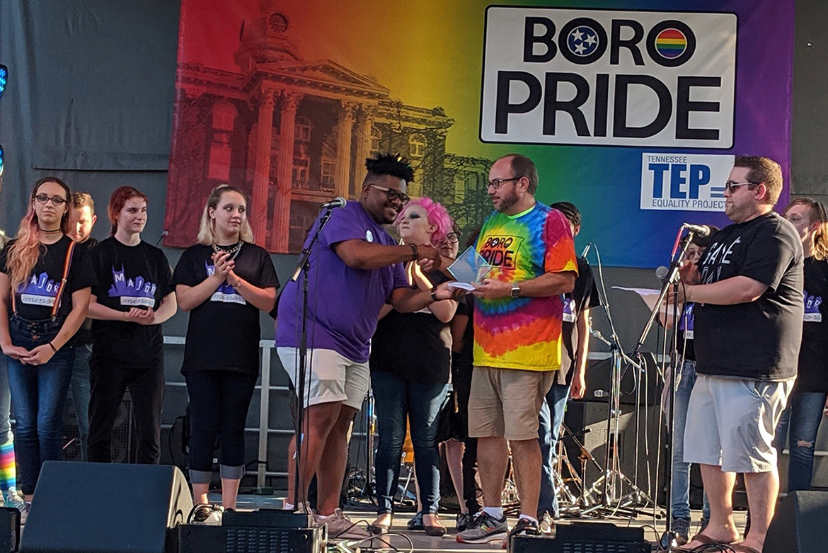 Tennessee Equality Project board member Paul Brisco, in purple shirt, presents the Champion of Equality Award to Will Langston, a psychology professor and faculty adviser to MT Lambda, during the Boro Pride festival Sept. 7 in Murfreesboro. At right, in black T-shirt, TEP Rutherford County Chair Justin Miller looks on. Both Brisco and Miller are MTSU alumni. (Photo provided)