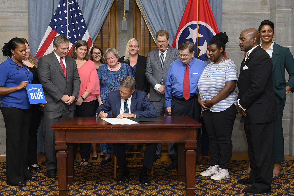 Tennessee Gov. Bill Lee, seated, conducted an official signing ceremony Aug. 20 for a new law to require state-supported colleges and universities to develop programs to help homeless students. Attending the signing are MTSU's Danielle Rochelle, far left, coordinator of outreach and support programs for MT One Stop; and next to her, Becca Seul, associate director at MT One Stop at MTSU. They were among several stakeholders, including state lawmakers and representatives from area educational institutions and nonprofits, also pictured and who advocated for the legislation. (Photo courtesy of Joy Kimbrough/Office of Gov. Bill Lee)