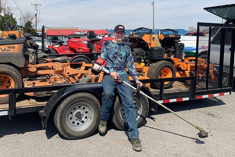 MTSU junior Nathan Fink of Horicon, Wisconsin, poses with the equipment he uses in his lawn-care business. Fink, a music business major and an entrepreneur since childhood, operates two businesses to pay for his college education and graduate debt-free. (Photo courtesy of Nathan Fink)