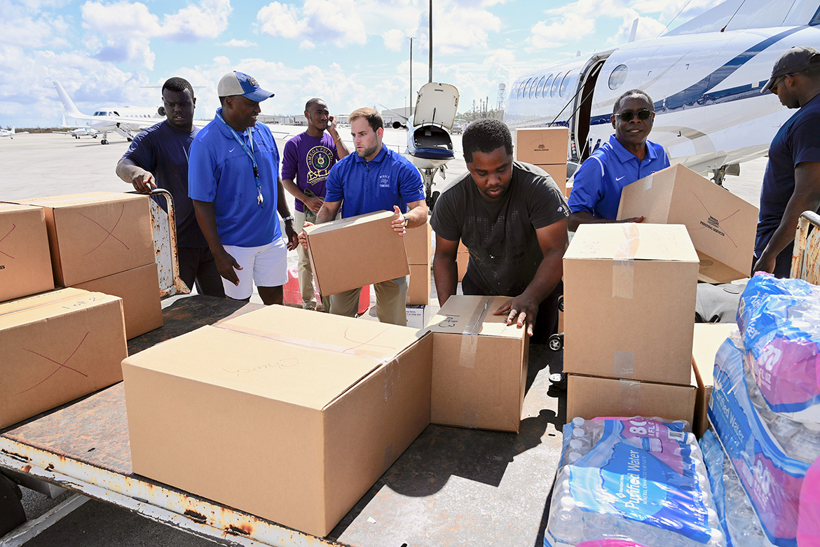 Officials and volunteers supporting MTSU's Raider Relief drive unload humanitarian supplies from one of two aircraft flown to Freeport, Bahamas, on Sunday, Sept. 8. (MTSU Photo by Andrew Oppmann)