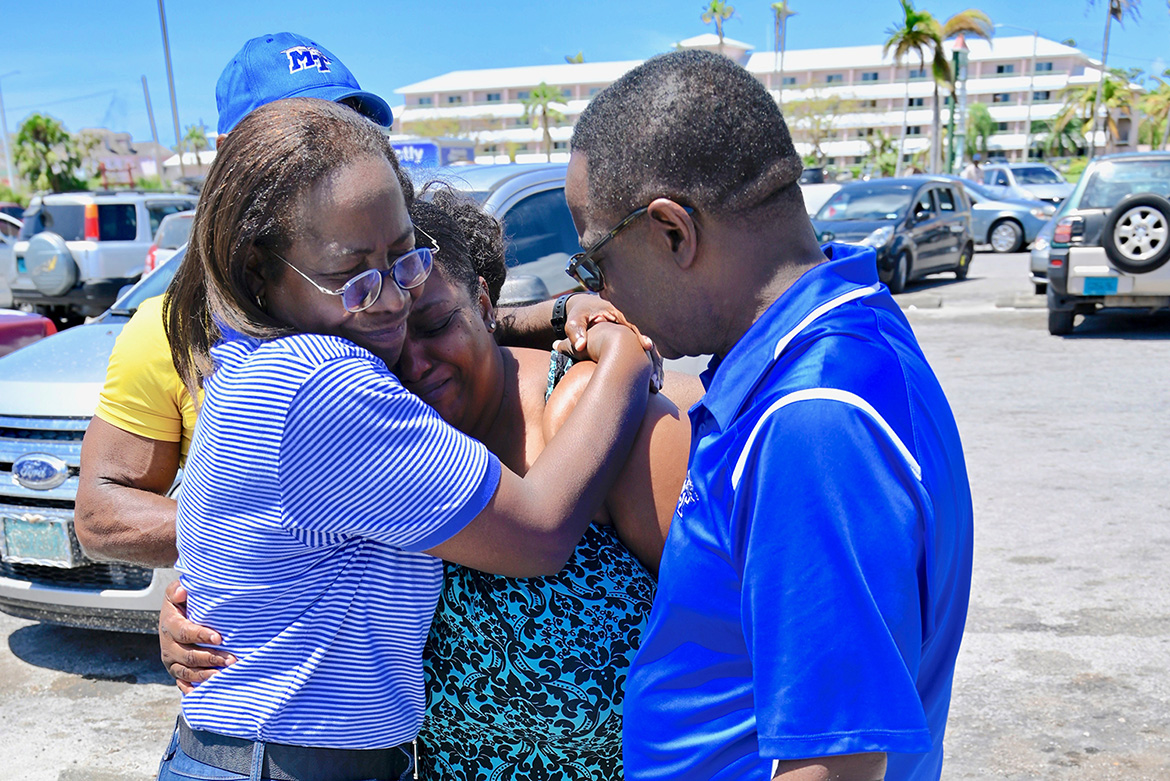 MTSU President Sidney A. McPhee, far right, consoles a Bahamian resident who was describing the loss of a family member when Hurricane Dorian made landfall. (MTSU Photo by Andrew Oppmann)