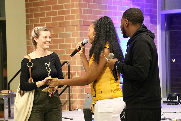 "Rep Your Roots second place winner Julia Cooper, left, accepts her trophy at this year's talent showcase held Friday, Sept. 20, in the Student Union atrium. Cooper, a junior in the College of Media and Entertainment, sang an original acoustic song title ""Footprints."" (Submitted photo)"