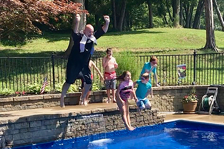 Dressed in cap and gown, Trey Lee, left, assistant superintendent of engineering and construction for Rutherford County Schools, jumps into his aunt's pool to celebrate the completion of a 30-year journey to earn his degree in construction management in August from MTSU courtesy of MTSU's flexible degree options. The Lee family held a special graduation celebration at his aunt's home. (Submitted photo)