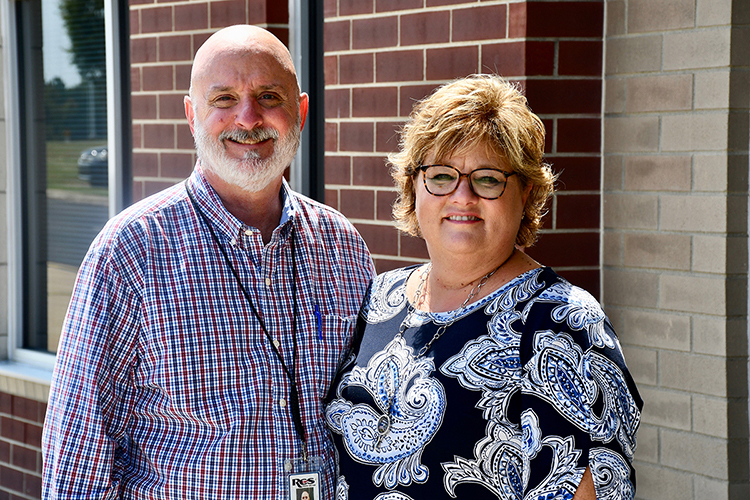 Trey Lee, left, assistant superintendent of engineering and construction for Rutherford County Schools, and his wife, Kim, pose for a photo on the campus of Stewarts Creek Middle School, where Lee's wife works. Lee completed a 30-year journey to earn his Bachelor of Science in Construction Management in August from MTSU courtesy of MTSU's flexible degree options. (Photo by MTSU Online)