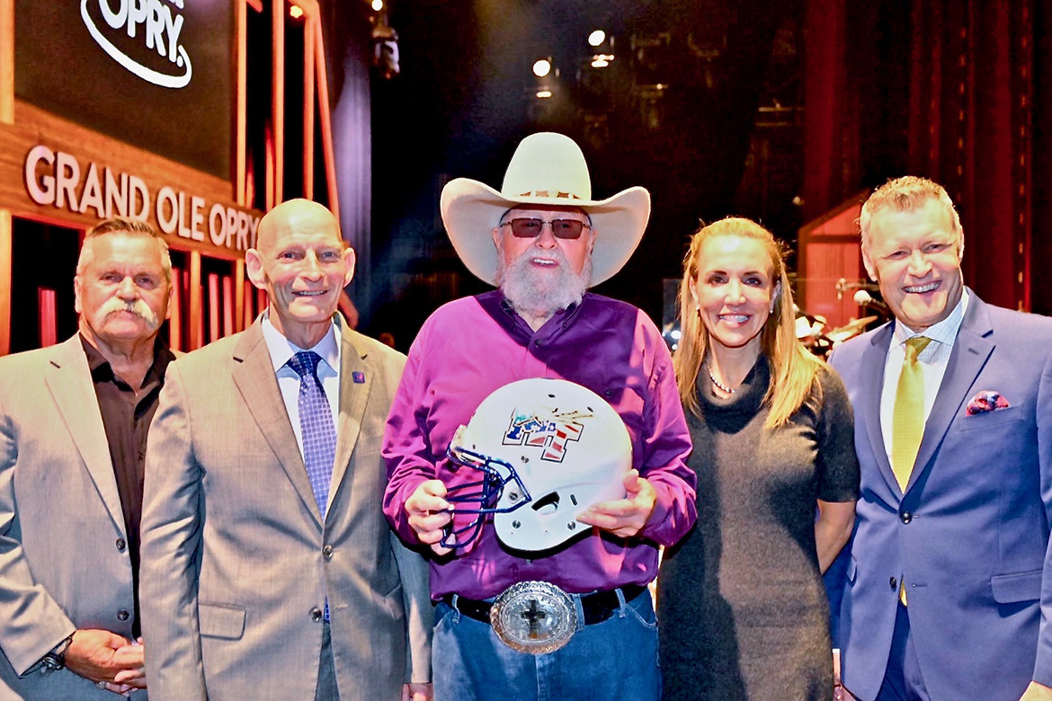Charlie Daniels, center, shows off his new Blue Raider Football helmet given to him by MTSU's Keith Huber, left of Daniels, and Hilary Miller, right of Daniels, after a surprise presentation at the Grand Ole Opry in Nashville, Tenn. In on the surprise was Daniels' long-time manager David Corlew, far left, and Opry announce Bill Cody, far right. (MTSU photo by Cat Curtis Murphy)