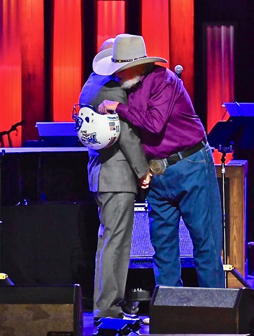 Country Music Hall of Famer Charlie Daniels, namesake and patron of MTSU's Charlie and Hazel Daniels Veterans and Military Family Center, embraces retired Army Lt. Gen. Keith Huber after Huber presented him a Blue Raider Football helmet. Huber surprised Daniels during an Oct. 15 show at the Grand Ole Opry in Nashville, Tenn. (MTSU photo by Cat Curtis Murphy)
