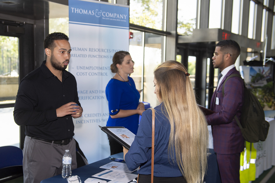 MTSU junior liberal arts major Justin McKlean, far right, and Jones College of Business alumna Hannah Kemp (Class of 2018), second from right, speak with recruiters from human resource consultant Thomas & Company of Nashville, Tenn., during the Oct. 3 MTSU Fall Career Fair at Murphy Center. (MTSU photo by James Cessna)
