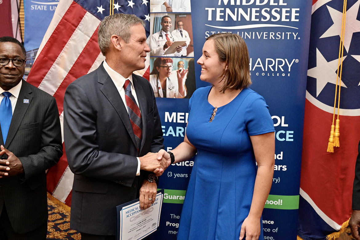 MTSU freshman Claire Ritter, right, shakes hands with Tennessee Gov. Bill Lee after Lee presented her with a special certificate Thursday, Oct. 3, in the State Capitol in Nashville. Ritter was one of six students recognized Thursday for their acceptance into the inaugural class of the Medical School Early Acceptance Program, a partnership between MTSU and Meharry Medical College to fast-track students to a medical degree in seven years through course work at both institutions. At far left is MTSU President Sidney A. McPhee. (MTSU photo by Andy Heidt)
