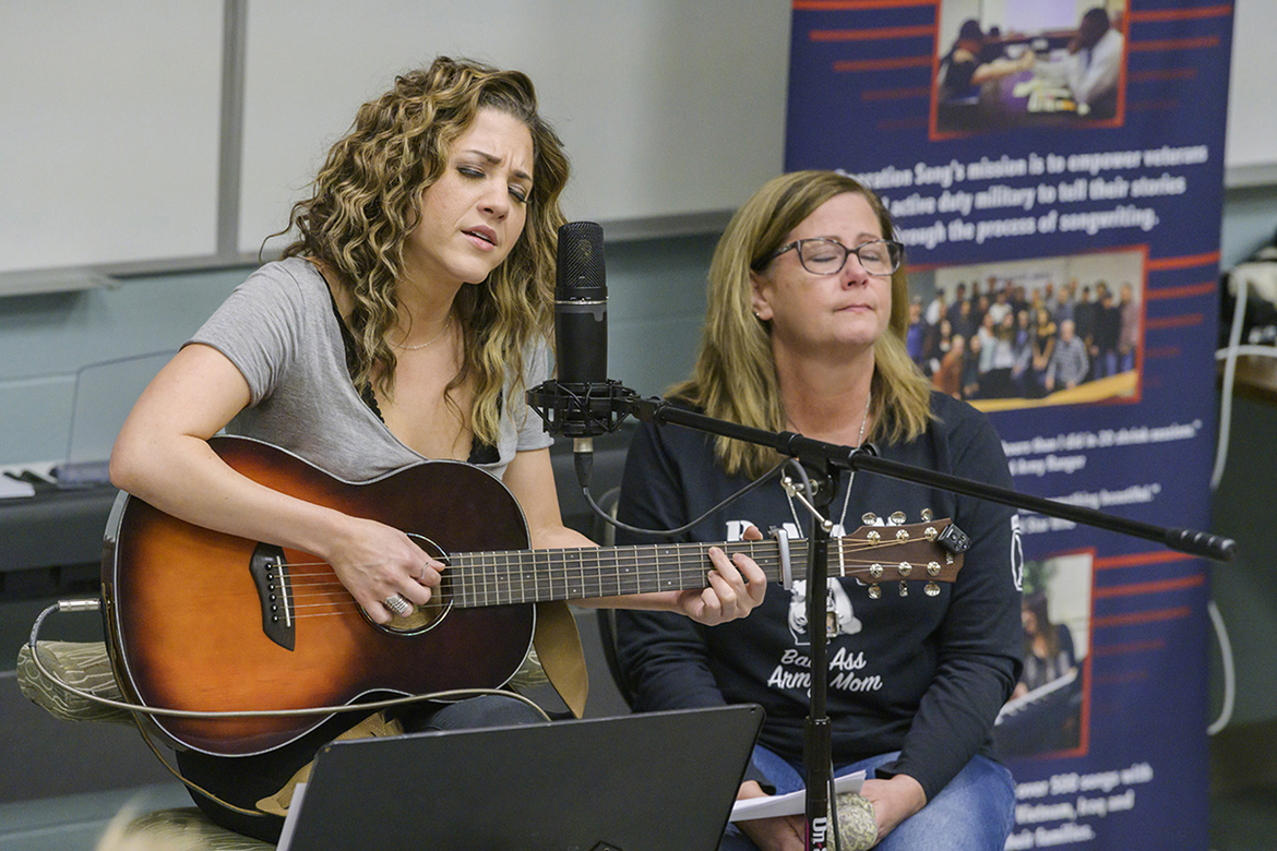 "Songwriter Jamie Floyd, left, plays and sings their new song while Jennifer Hyde of Murfreesboro, a U.S. Army mom and executive aide for the dean of MTSU's College of Education, listens at a special showcase for Operation Song's fourth annual ""Songs and Stripes"" event at MTSU Friday, Oct. 25. The event teams trios of military veterans, student and professional songwriters to create healing music for the veterans and training for the students. Not pictured is co-writer Abby Gibson, a senior commercial songwriting major from Roswell, Georgia. (MTSU photo by Andy Heidt)"