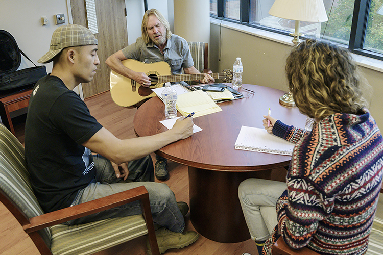 "Songwriter Rob Crosby, center, plays a potential chorus of their new song while Nate Tiuseco of Readyville, Tennessee, left, a retired Marine and MTSU sophomore photography major, and senior songwriting major Faith Cotto of Murfreesboro make notes during their writing session at Operation Song's fourth annual ""Songs and Stripes"" event at MTSU Friday, Oct. 25. The event teams trios of military veterans, student and professional songwriters to create healing music for the veterans and training for the students. (MTSU photo by Andy Heidt)"