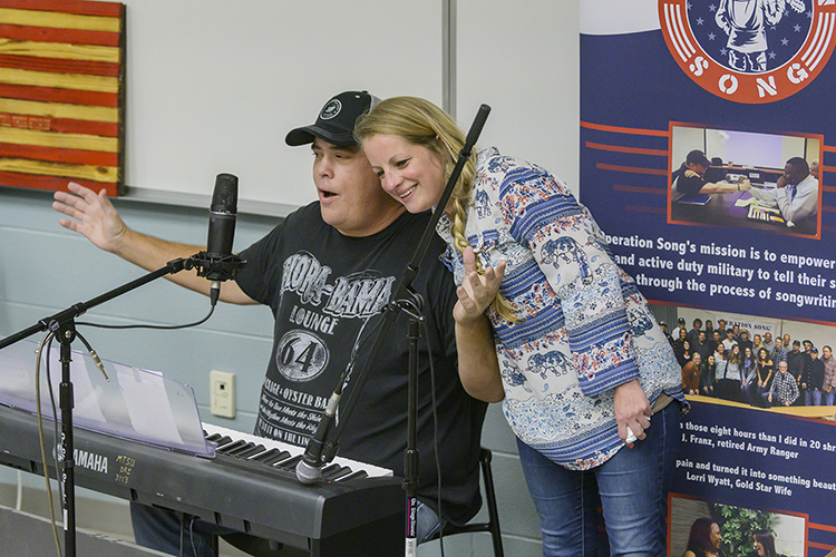 "Elizabeth Wilburn of Murfreesboro, a U.S. Army veteran and the office manager for MTSU's Charlie and Hazel Daniels Veterans and Military Family Center, leans on songwriter Pete Sallis as he cuts up before performing their new song at a special showcase for Operation Song's fourth annual ""Songs and Stripes"" event at MTSU Friday, Oct. 25. The event teams trios of military veterans, student and professional songwriters to create healing music for the veterans and training for the students. Not pictured is co-writer Shamarra Chalk, a senior commercial songwriting major from Blytheville, Arkansas. (MTSU photo by Andy Heidt)"