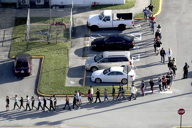 Police help students and staff evacuate Marjory Stoneman Douglas High School in Parkland, Fla., Feb. 14, 2018, after a shooter opened fire on the campus. Three staffers from the South Florida Sun Sentinel will discuss the paper's 2019 Pulitzer Prize for public service journalism at MTSU Tuesday, Oct. 22. (Mike Stocker/South Florida Sun-Sentinel)