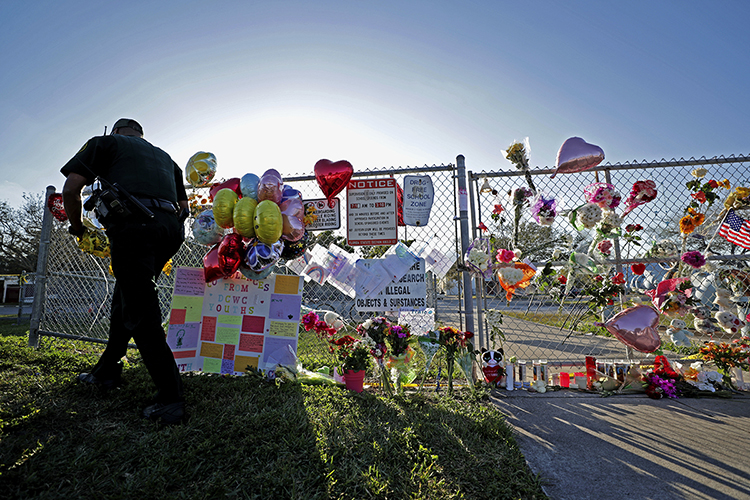 A Broward County Sheriff's Office deputy removes police tape from a makeshift memorial at Marjory Stoneman Douglas High School in Parkland, Fla., Sunday, Feb. 18, 2018, four days after a former student went on a shooting spree at the school, killing 17 and injuring 17 more. Three staffers from the South Florida Sun Sentinel will discuss the paper's 2019 Pulitzer Prize for public service journalism at MTSU Tuesday, Oct. 22. (John McCall/South Florida Sun Sentinel)