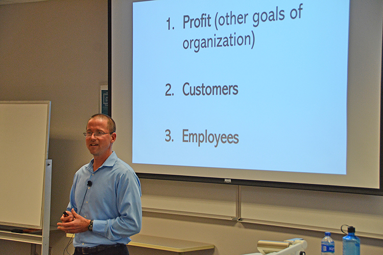 Social entrepreneur and author Matt Tenney talks to MTSU management students about the value of servant leadership during a guest lecture Thursday, Oct. 17, inside the Business and Aerospace Building classroom. The slide behind him shows the traditional approach to business where profit is the top priority. Tenney told students that employees should be at the top instead and the profits will follow. (MTSU photo by Jimmy Hart)