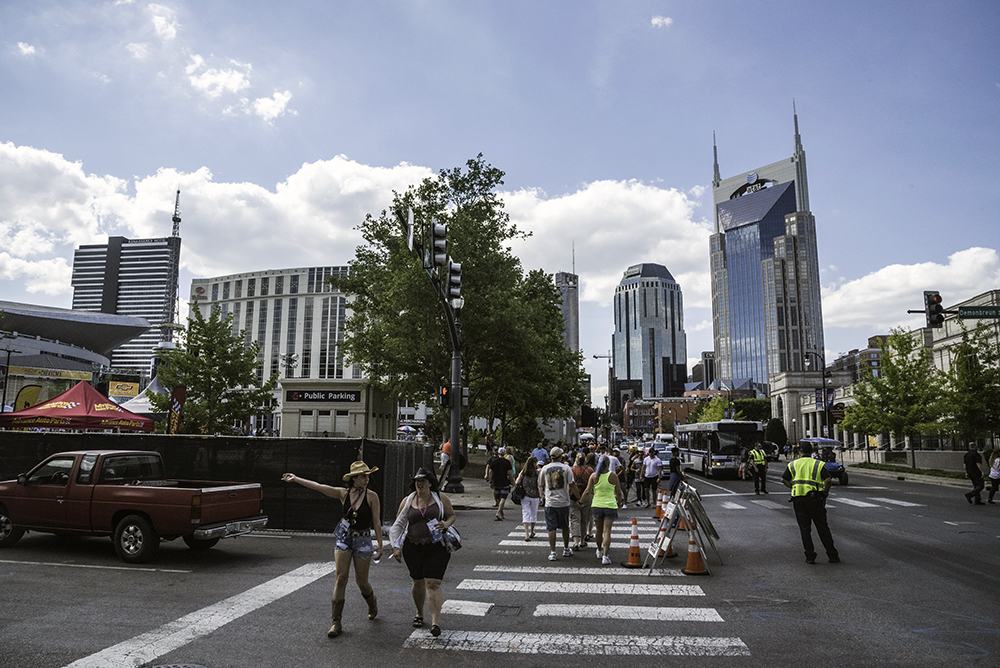 Pedestrians cross Demonbreun Street at Fourth Avenue South in downtown Nashville near the Music City Walk of Fame Park and the Schermerhorn Symphony Center as the city skyline rises behind them.