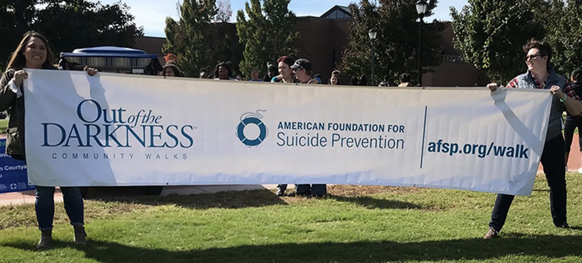 MTSU graduate students Lisa Hattaway, left, and Sarah Elmer, both social work majors, hold a banner touting community walks promoting suicide awareness at the 2018 Hike for Life. (Photo submitted)