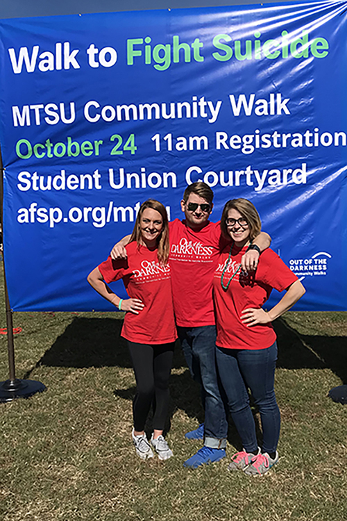 Organizers of Hike for Hope pose in front of a banner during the 2018 event. From left, Kat Cloud, Tennessee area director for the American Foundation for Suicide Prevention; Justin Bucchio, assistant professor of social work and coordinator of the social work master's degree program; and Sarah Pope, psychology major. (Photo submitted)