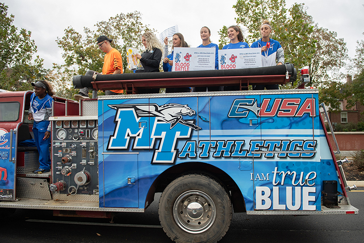 "Student volunteers, led by Chelsea Floyd, left, MTSU assistant athletic director for marketing, wave banners and toss candy from a customized antique fire truck at the 2019 homecoming parade to reach hundreds of university supporters and encourage crowds to ""Bleed Blue, Beat WKU"" during the annual blood drive competition Monday-Wednesday, Nov. 18-20. The event will be held at the Campus Recreation Center gym, 1848 Blue Raider Drive, from 11 a.m. to 6 p.m. each day. You can make an appointment today at http://bit.ly/MTSUBleedBlue2019. (MTSU photo by James Cessna)"