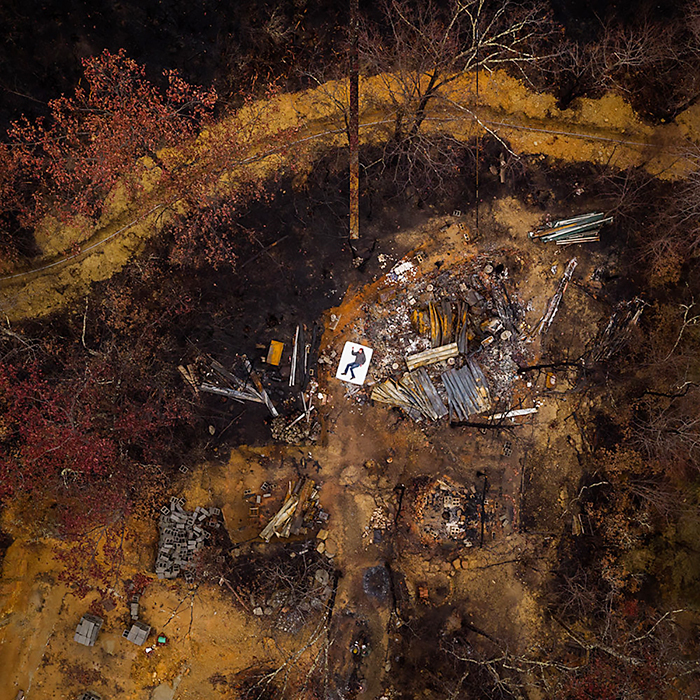 "Kirk Fleta rests on a white mattress in the ashen ruins of his home, destroyed in the deadly 2016 wildfires that swept through portions of the Great Smoky Mountains, devastating Gatlinburg, Pigeon Forge and more than 10,000 acres of the national park in this aerial photo captured by MTSU alumnus and photographer/entrepreneur Jeremy Cowart for his ""Voices of Gatlinburg"" project. (Photo by Jeremy Cowart)"