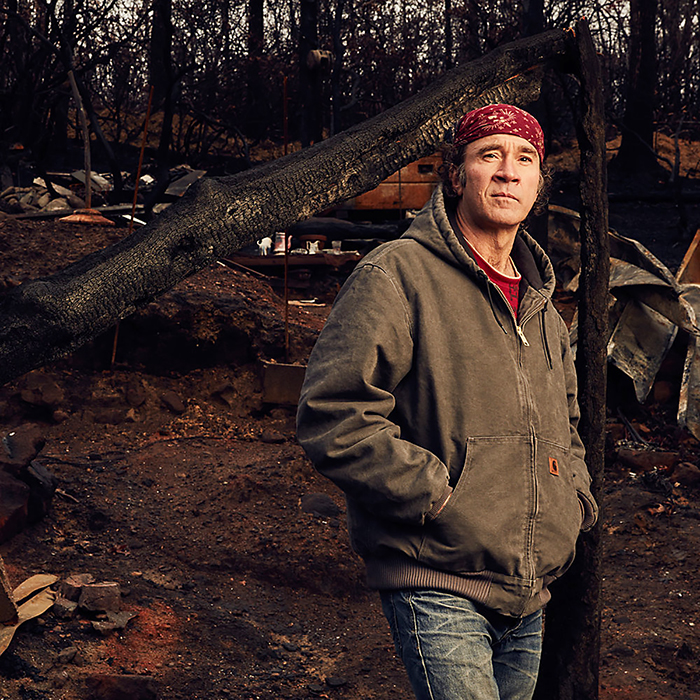 "Kirk Fleta pauses in the ashen ruins of his home, destroyed in the deadly 2016 wildfires that swept through portions of the Great Smoky Mountains, devastating Gatlinburg, Pigeon Forge and more than 10,000 acres of the national park in this photo captured by MTSU alumnus and photographer/entrepreneur Jeremy Cowart for his ""Voices of Gatlinburg"" project. Cowart's work will be on exhibit at MTSU's Baldwin Photographic Gallery Nov. 25-Jan. 31. (Photo by Jeremy Cowart)"