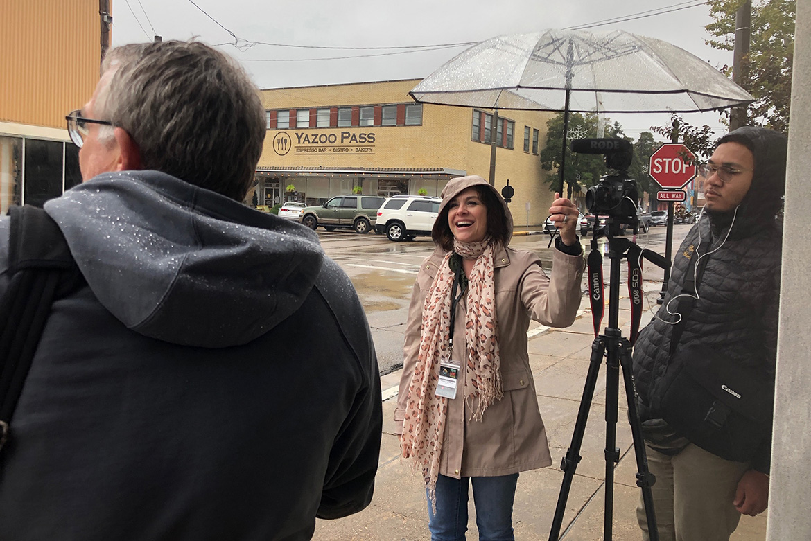 Christine Eschenfelder, center, an assistant professor in the MTSU College of Media and Entertainment's School of Journalism and Strategic Media, protects herself and the video camera from the rain at a Clarksdale, Miss., location during the recent Lens Collective 2019 multimedia storytelling workshop at the University of Mississippi. (Submitted photo)