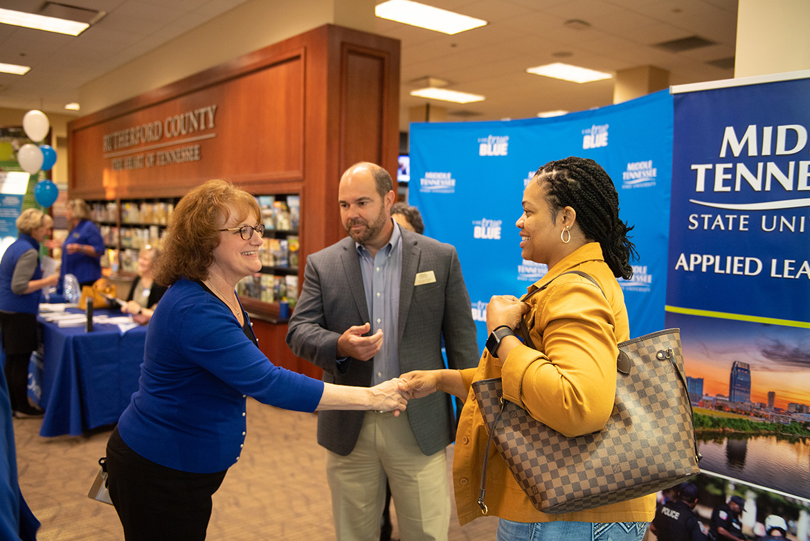 MTSU University College's Peggy Carpenter, left, assistant dean, and John Burchfield, director of finance and administration, speak to a prospective student at the Finish Your Degree Q and A event held Oct. 23 at the Rutherford County Chamber of Commerce in Murfreesboro, Tenn. (MTSU photo by James Cessna)