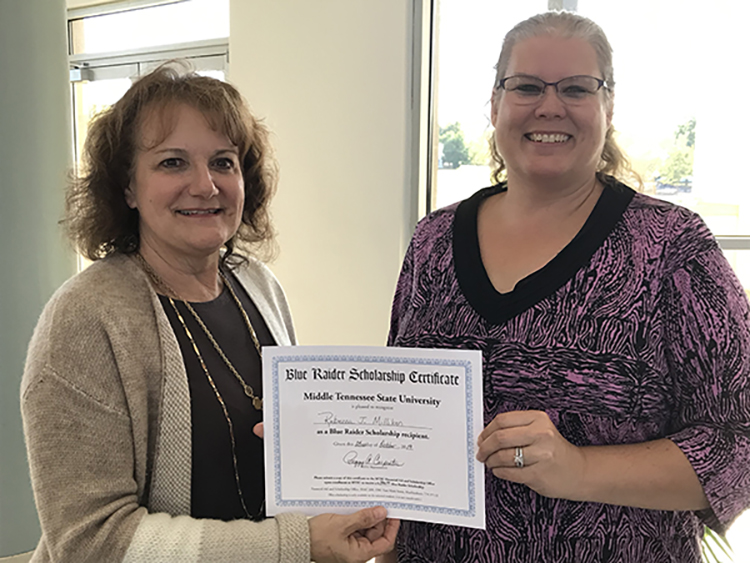 Peggy Carpenter, assistant dean of University College, presents Becky Milliken with a scholarship certificate at the Finish Your Degree Q&A event held Oct. 23 at the Rutherford County Chamber of Commerce in Murfreesboro, Tenn. (MTSU photo by Hunter Patterson)