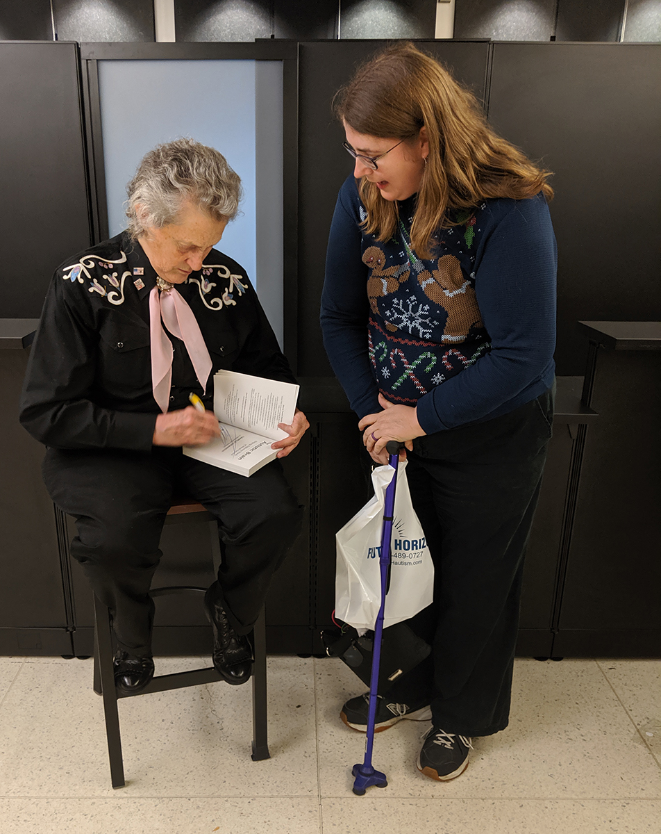 "Temple Grandin, left, autographs a copy of her book, ""The Autistic Brain: Helping Different Kinds of Minds Succeed,"" she co-wrote with Richard Panek, for Bonnie McCarty, an adviser in the College of Behavioral and Health Science, Monday, Nov. 11. Grandin spoke to a sold-out crowd in Tucker Theatre. (Submitted photo)"