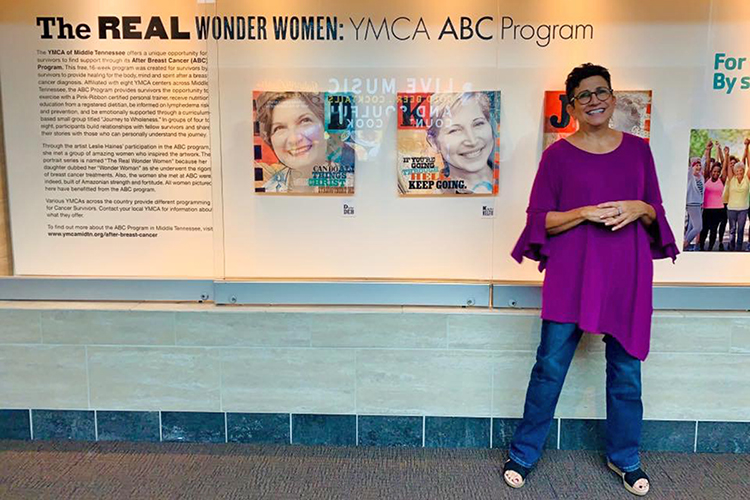 "Leslie Haines, a visual communication professor in the MTSU School of Journalism and Strategic Media and breast cancer survivor, poses in front of her work at the Nashville International Airport in September for a special reception for her art exhibit on display. Haines created a series of 12 portrait illustrations of fellow breast cancer survivors titled ""The Real Wonder Women: YMCA ABC Program"" that will be on display until late February. (Submitted photo)"