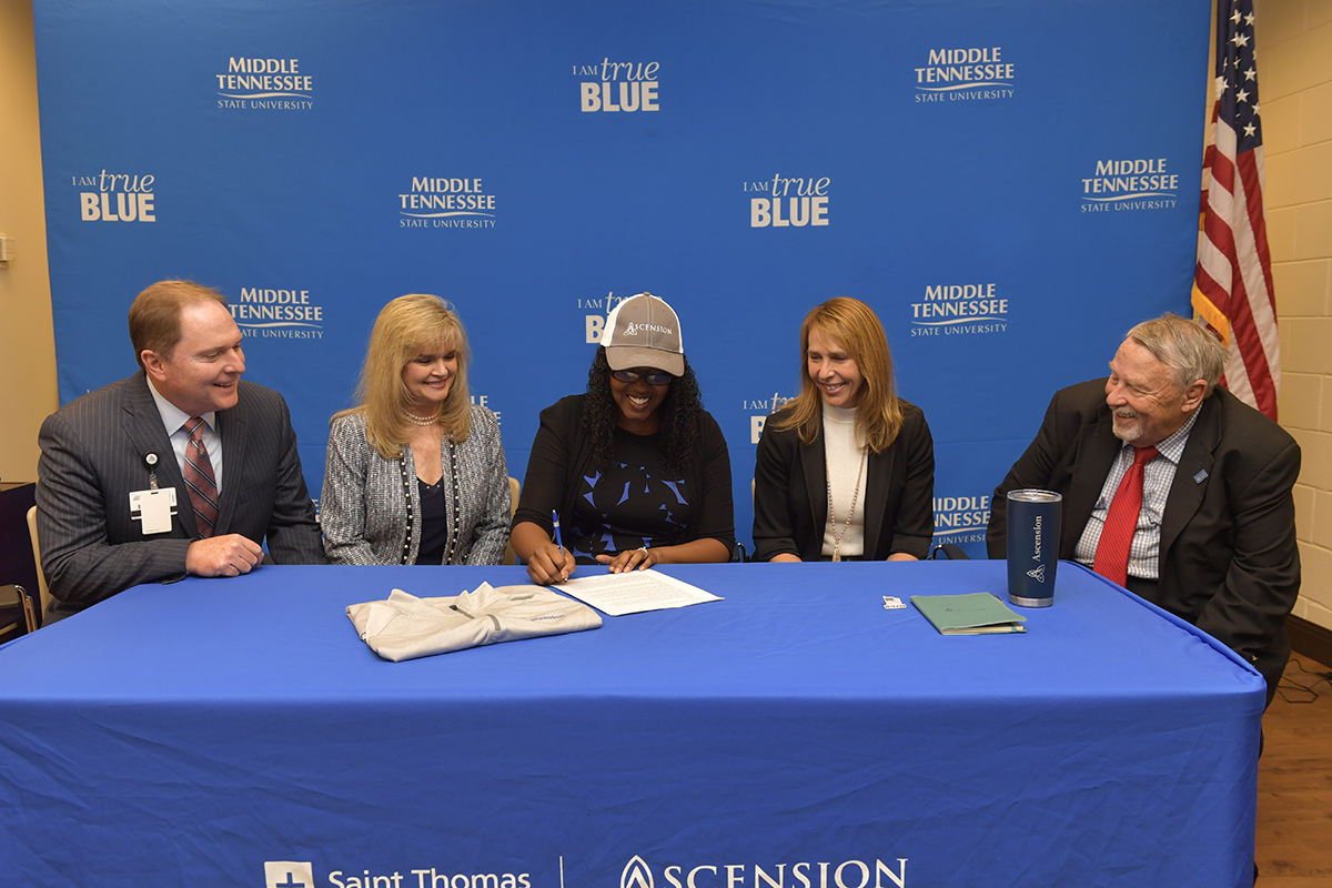 MTSU student veteran Martinna Young, center, signed an agreement making her the inaugural member of the Ascension Saint Thomas Nursing Corps, a partnership with MTSU that seeks to create a robust pipeline of strong registered nurse candidates who are also military veterans. Ascension Saint Thomas CEO and President Tim Adams, left, MTSU School of Nursing Director Jenny Sauls, Ascension Saint Thomas COO Michelle Robertson and MTSU College of Behavioral and Health Sciences Dean Terry Whiteside viewed the signing Tuesday, Nov. 26, in the Daniels Veterans Center on the MTSU campus. (MTSU photo by James Cessna)
