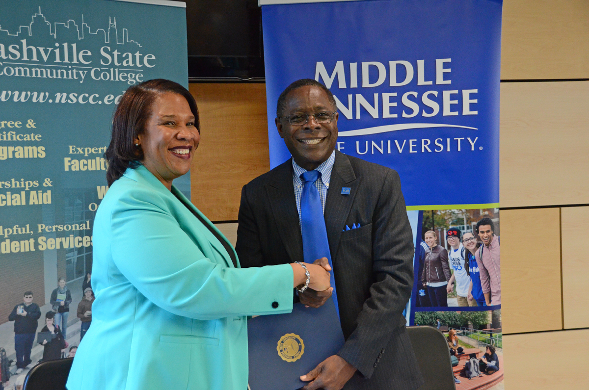 "Presidents Shanna L. Jackson, left, of Nashville State Community College and Sidney A. McPhee of Middle Tennessee State University sign an agreement marking the ""True Blue Pathway"" to Nashville State, the eighth such agreement established for students with associate degrees to move seamlessly to the four-year university. The signing occurred Nov. 20 at Nashville State's main campus on White Bridge Road in Nashville. (MTSU photo by Randy Weiler)"