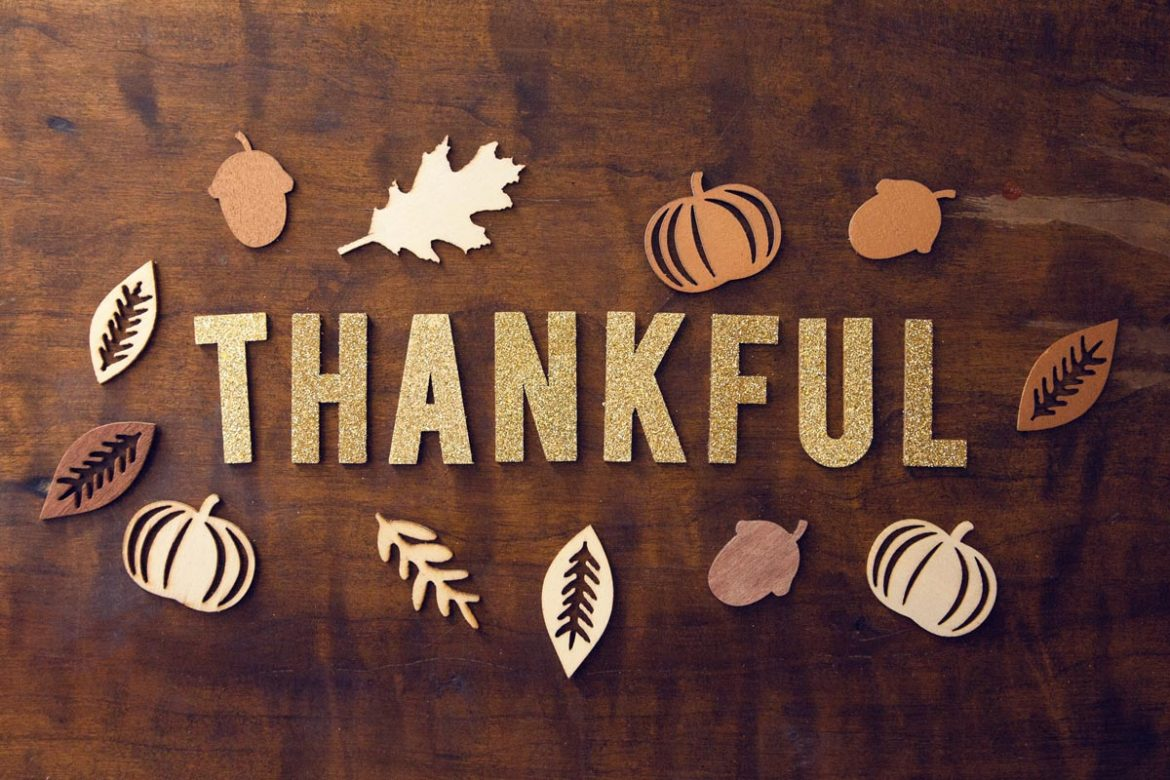 Tabletop photo of block letters spelling Thankful surrounded by Thanksgiving themed cutouts. Photo by Pro Church Media on Unsplash.