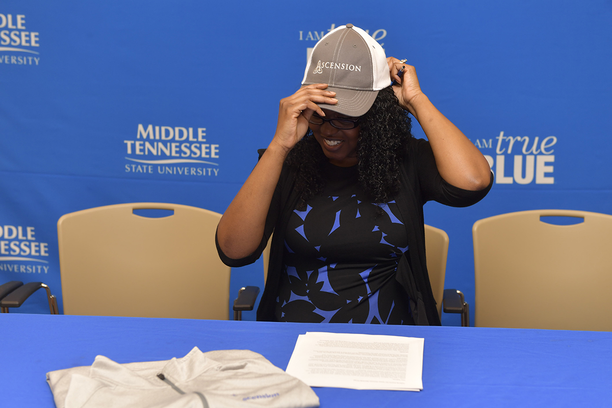 MTSU student veteran Martinna Young of Murfreesboro tried on an Ascension baseball cap during the inaugural signing for her to be the first member of the Saint Thomas Nursing Corps Tuesday, Nov. 26, at the Charlie and Hazel Daniels Veterans and Military Family Center inside the Keathley University Center. (MTSU photo by James Cessna)