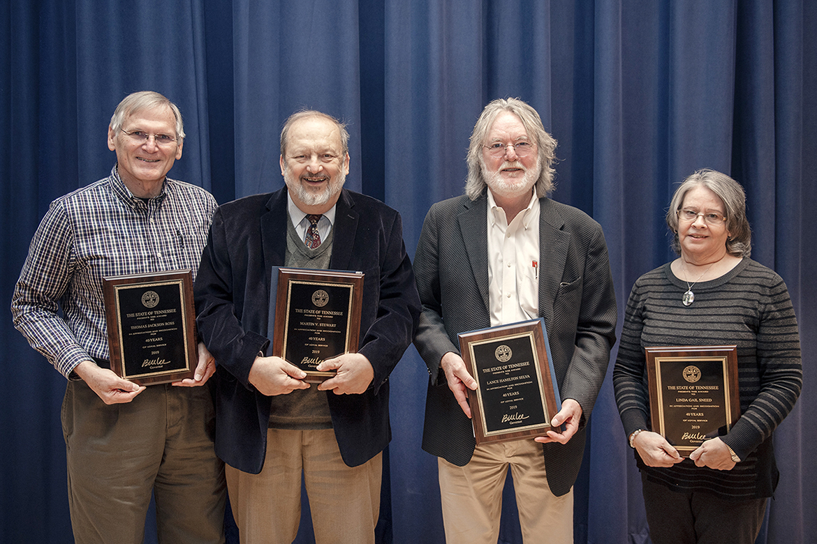 MTSU employees honored for 40 years of service to the university pose with plaques recognizing their work at the university's annual Service Award Luncheon, held Dec. 5 in the James Union Building. More than 230 faculty and staff members were saluted at the 2019 event for their years of service. From left are Jack Ross of Estill Springs, Tenn., Division of Marketing and Communications; and Martin Stewart, Department of Chemistry; Lance Selva, Department of Criminal Justice Administration; and Gail Sneed of Department of Media Arts, all Murfreesboro residents. (MTSU photo by James Cessna)