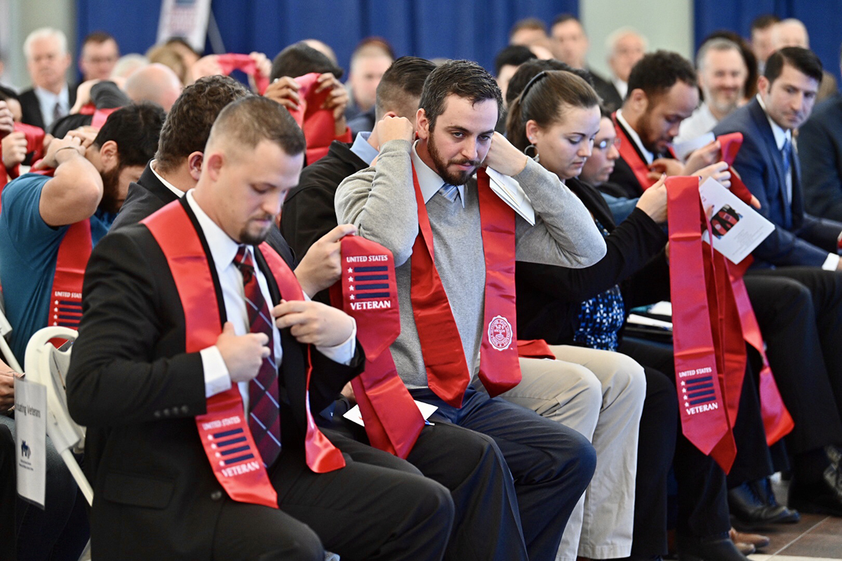 MTSU seniors adjusted the red stoles they had just received before the 15th Graduating Veterans Stole Ceremony at the Miller Education Center Wednesday, Dec. 4. They can wear the stoles during commencement ceremonies Saturday, Dec. 14, in Murphy Center. (MTSU photo by J. Intintoli)
