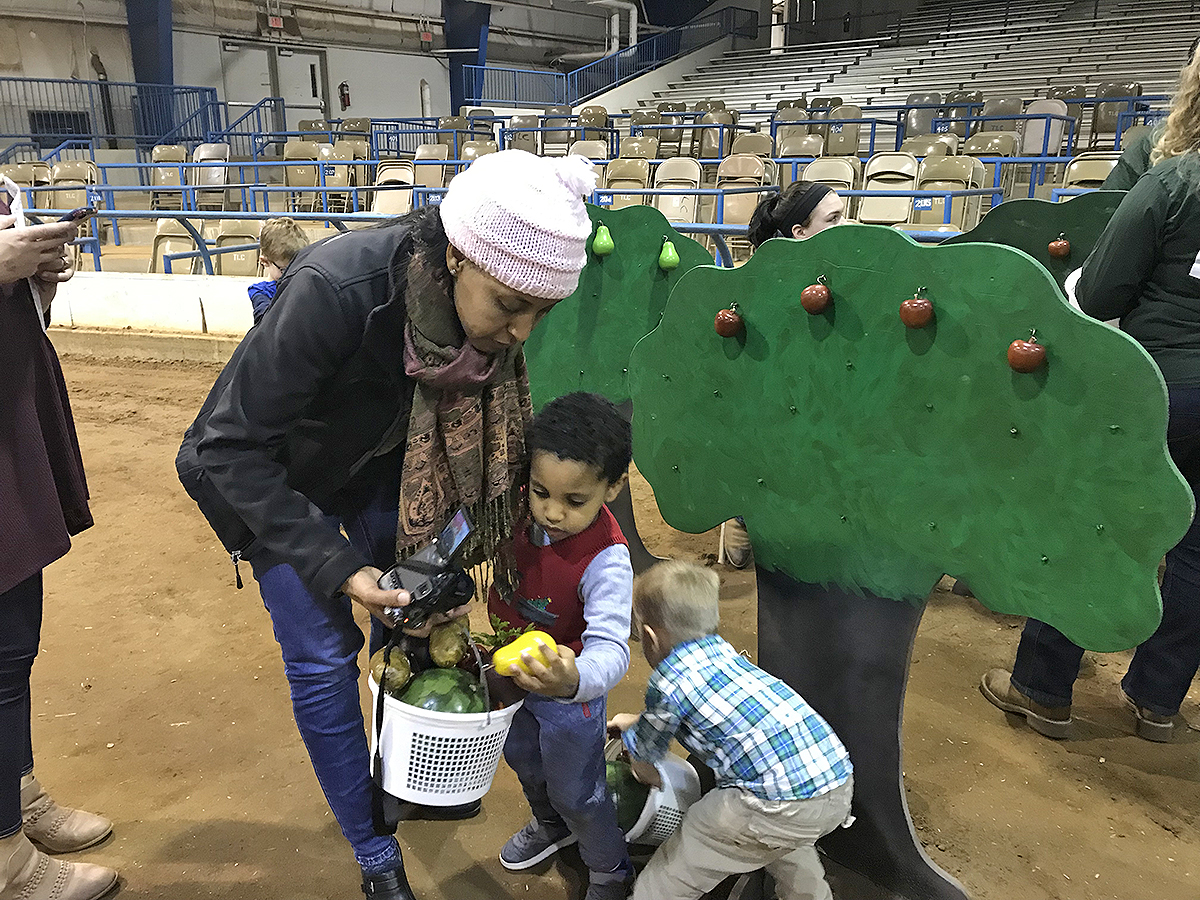 "Mom Sara Kedanu, left, of Nashville, Tenn., helped her son Luke Wynne, 3, collect fruits and vegetables in the Little Acres section of the MTSU Agritourism Club's Winter Village Dec. 7 in the Tennessee Livestock Center on Greenland Drive. Wynne's father, Daniel Wynne, is an assistant director in housing and residential life at MTSU. Held annually, Winter Village is one of Luke Wynne's ""favorite things to do during Christmas,"" Sara Kedanu said. (MTSU photo by Randy Weiler)"