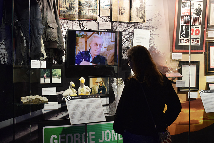"An MTSU recording industry student closely inspects memorabilia during a special tour of the George Jones Museum in downtown Nashville by the university's experiential learning class, ""The Life and Music of George Jones,"" taught by Commercial Songwriting Program director Odie Blackmon. Included in this case is a piece of the bridge Jones crashed his SUV into in 1999, a near-fatal wreck he and his wife, Nancy, credited with saving his life. Nancy Jones, who supplied the museum items with her husband's guidance before his 2013 death, visited with the Jones class the day before the tour to discuss the couple's adventures. (Photo courtesy of Odie Blackmon"