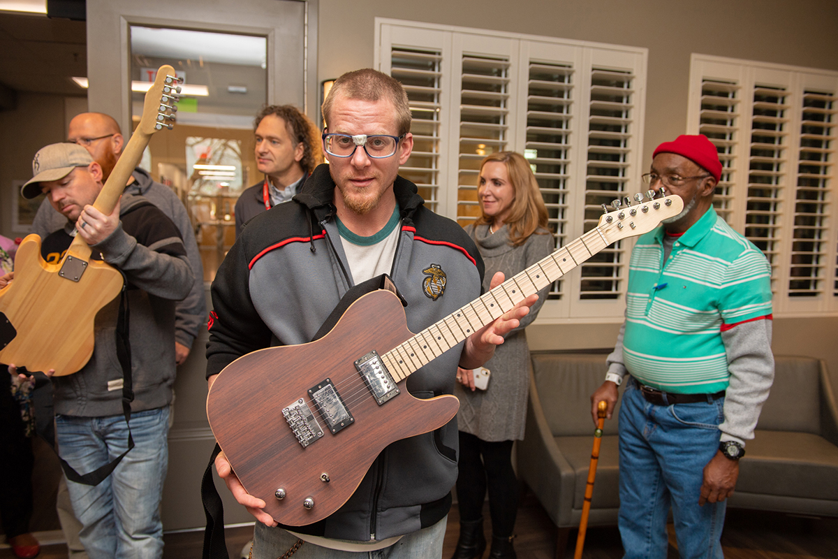 U.S. Marine veteran Joshua Boatman, foreground, holds one of four electric guitars given to the Alvin C. York Veterans' Administration Medical Center recently by MTSU and Schneider Electric for music therapy as others watched while participating in the small presentation in Building 17, also called the Residential Rehab Treatment Program facility. (MTSU photo by James Cessna)