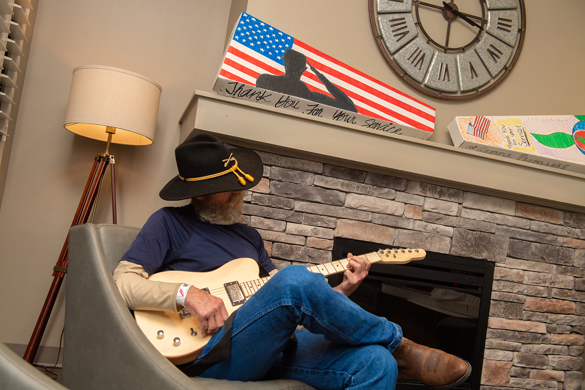 U.S. veteran Phillip Rich sat near the fireplace in the recreation room at the Alvin C. York Veterans' Administration Medical Center and played around with one of four guitars given for music therapy at the veterans facility by MTSU and Schneider Electric. On the mantle are two of the military-themed, hand-painted boxes for two of four guitars given recently. (MTSU photo by James Cessna)