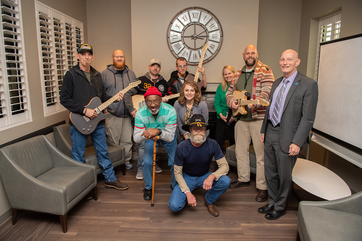 A recent gift of four guitars to the Alvin C. York Veterans' Administration Medical Center will be used for music therapy by patients. Attendees of the Dec. 3 instrument announcement included Phillip Rich, kneeling front; Mark Davis, left, and Schneider Electric's Karen Mallard, kneeling second row; and Levi Troxell, back row left, Micheal Strong, Justin Haverlin, Joshua Boatman, Tennessee Valley Healthcare System Director Jennifer Vedral-Baron, VA addiction therapist Martin David and MTSU's Keith M. Huber. (MTSU photo by James Cessna)