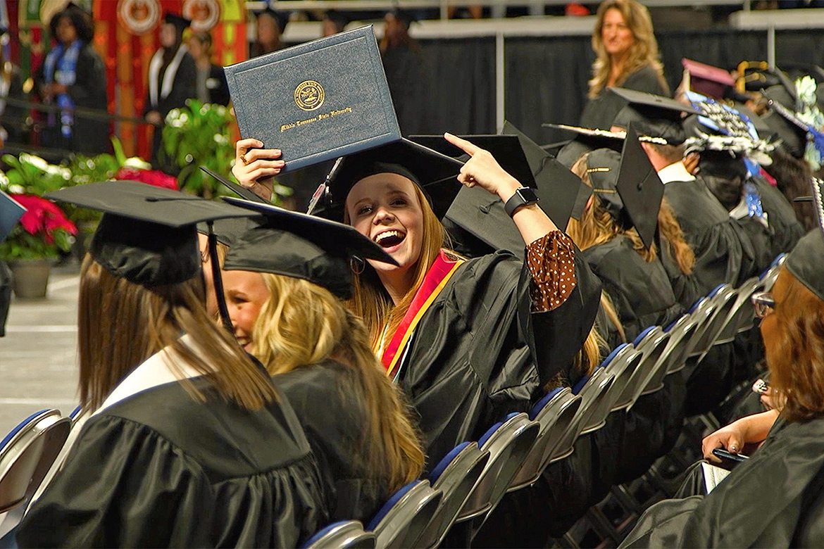 A new MTSU graduate shows her degree to family and friends in the audience at Murphy Center at the university's fall 2019 commencement event in this file image. MTSU, which held virtual graduations for its May and August 2020 graduates because of the pandemic, held three outdoor events last fall. Spring 2021 graduates will return to Murphy Center May 7-9 for the first time since 2019 for a three-day, 10-event, socially distanced commencement weekend. (MTSU file photo by Joe Poe)